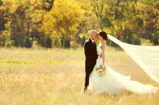Bride and groom get their picture taken in a field before their wedding.